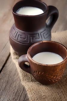 粘土のピッチャーで新鮮な牛乳。