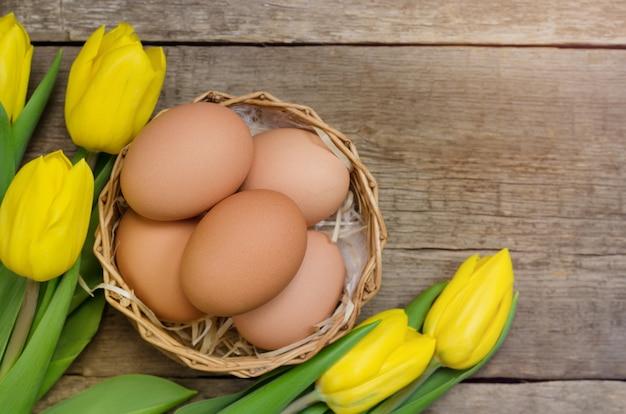黄色のチューリップとイースターデコレーションのために準備された新鮮な卵。