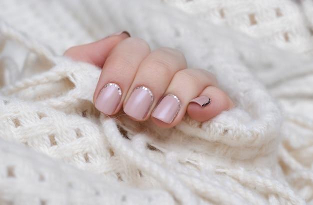 ピンクの爪を持つ女性の手