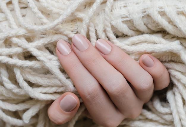 Красивая женская рука с бежевым дизайном ногтей