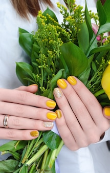 女性の手の中の黄色い花。