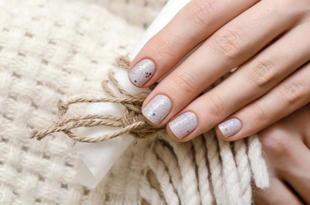 Женские руки с белым блеском дизайна ногтей.