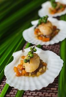 Обжаренные морские гребешки подают на ложе из овощей на скорлупе.