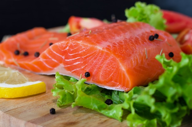Филе лосося с листьями салата, лимоном и черным перцем