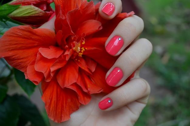 Женская рука с блестящим розовым маникюром