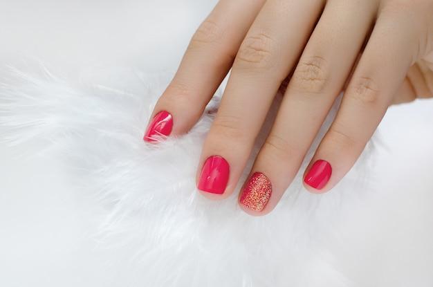 ピンクのマニキュアと白い羽の女性の手。