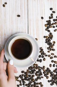 一杯のコーヒーと木製の背景にコーヒー豆