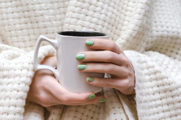 Женские руки с блеском зеленого дизайна ногтей