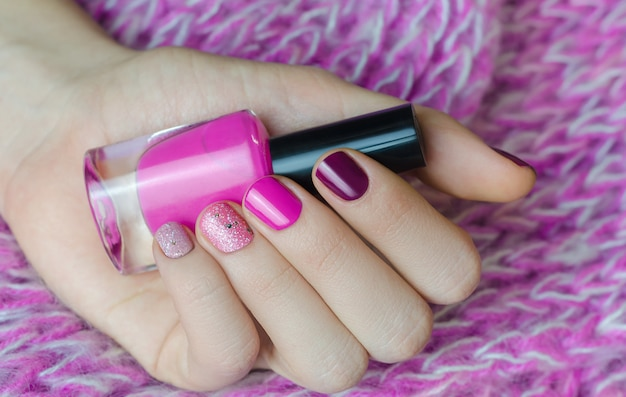 Нейл арт с блеском. красивая женская рука с розовым маникюром