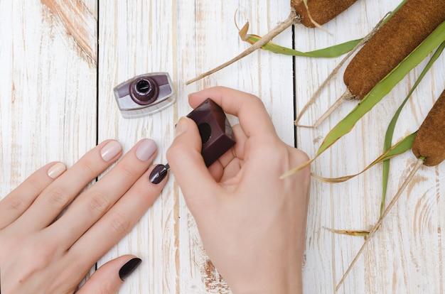 Женщина красит ее ногти в коричневый цвет.