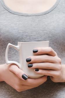 Женские руки с черным матовым дизайном ногтей.