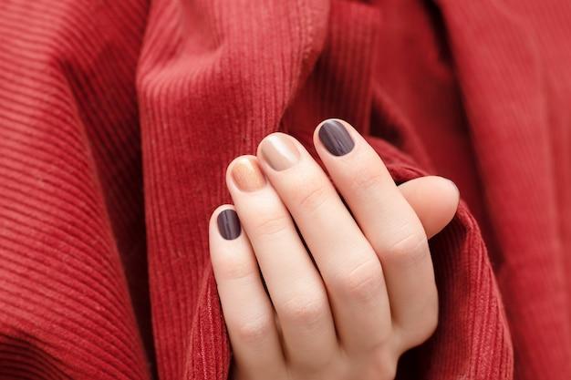 ブラウンのネイルデザイン。キラキラのマニキュアで女性の手。