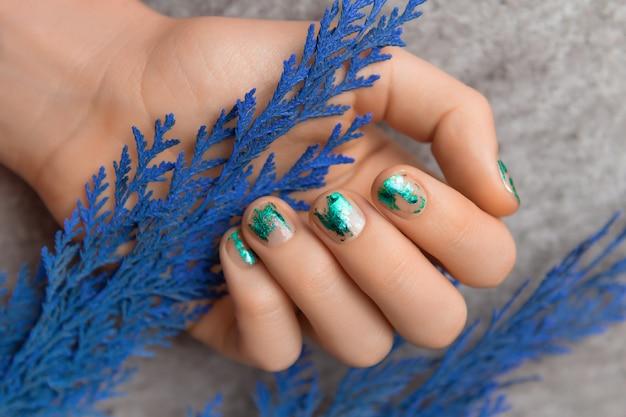 緑の箔ネイルデザインの女性の手