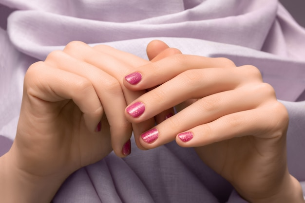 ピンクのグリッターネイルデザインの女性の手。