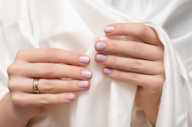 ピンクのネイルデザイン。キラキラのマニキュアで女性の手。