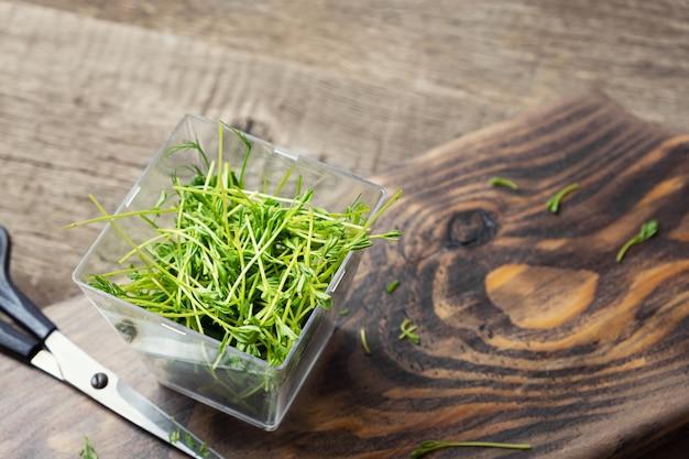 マイクログリーン。木製の背景にレンズ豆の芽。