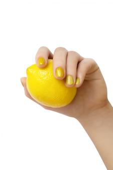 レモンを保持しているキラキラのマニキュアで女性の手