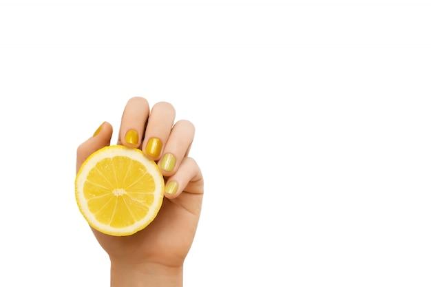 黄色のネイルデザイン。レモンを保持しているキラキラのマニキュアで女性の手。