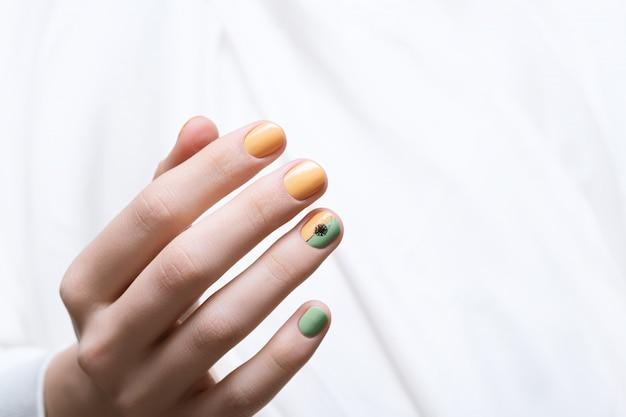緑の爪のデザイン。タンポポのネイルアートで女性の手。