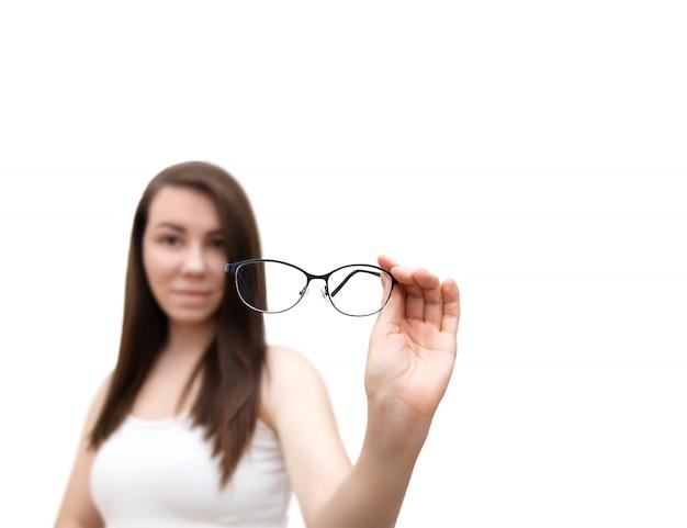 女性は、白い背景で隔離の眼鏡を手に保持しています。眼鏡のセレクティブフォーカス。