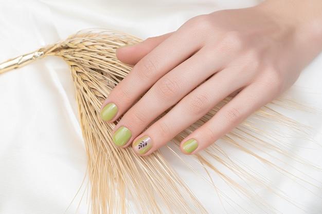 Зеленый дизайн ногтей. женская рука с блеском маникюра.