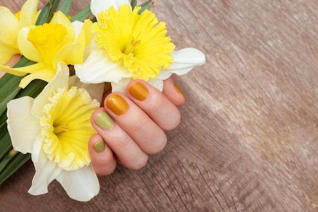 Желтый дизайн ногтей. женская рука с блеском маникюр, холдинг нарцисс цветы.