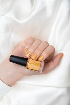 黄色のネイルデザイン。キラキラのマニキュアで女性の手。