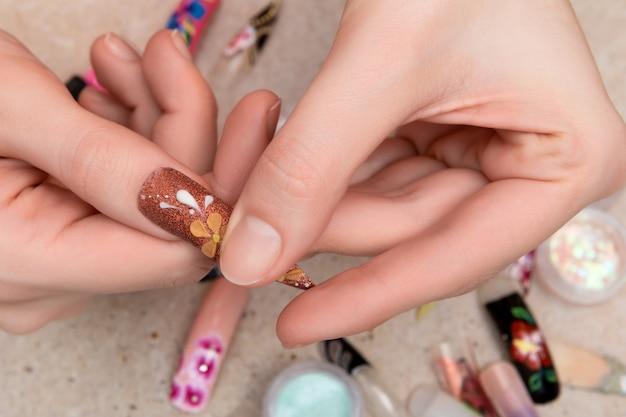 花のネイルデザインで人工爪のヒントを試す女の子