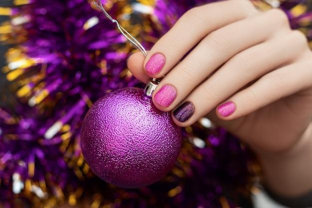 クリスマスと新年のネイルデザインの女性の手はきらびやかなおもちゃの球体を保持します。