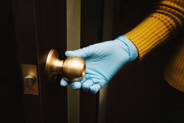保護手袋の女性の手がドアを開ける