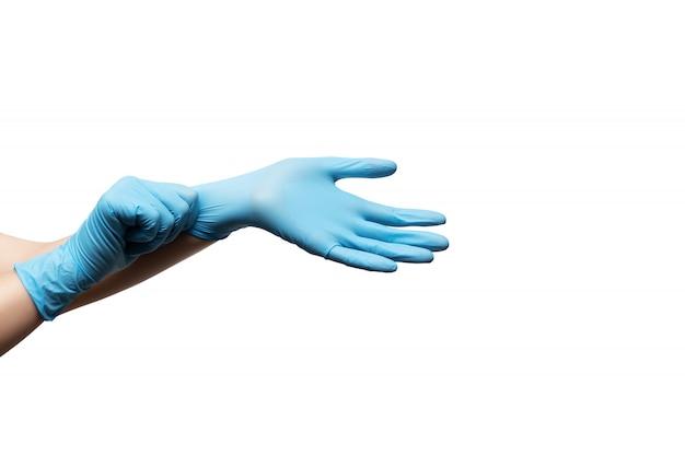 白い背景の上の使い捨て手袋の女性の手。