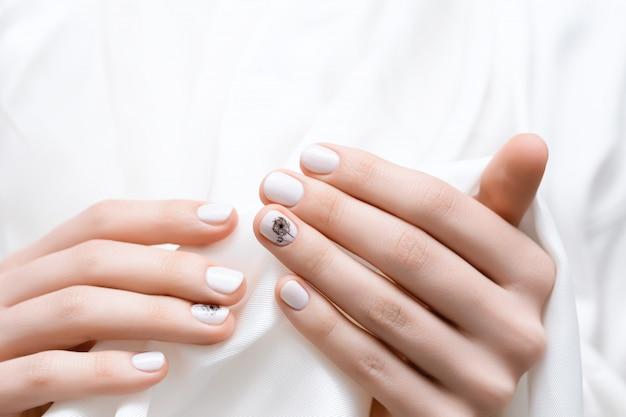 白いタンポポのネイルデザインの女性の手。