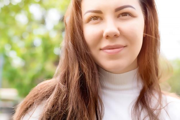 緑の春の庭で笑顔の若い女性