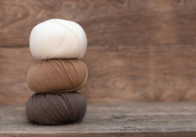 Крупным планом шерсти, вязание на деревянных фоне