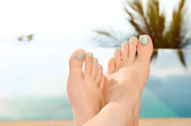 女性の足のクローズアップ。プールサイドでリラックスした女の子。