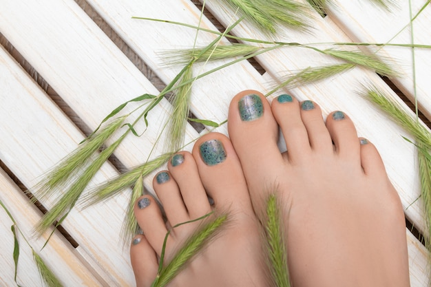 青いキラキラペディキュアと美しい女性の足
