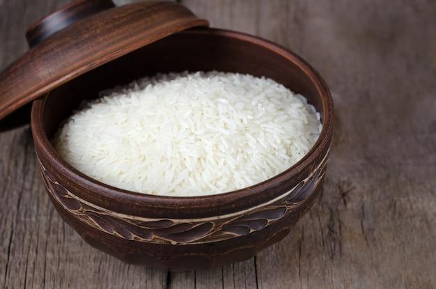木製の背景に粘土ボウルで調理米