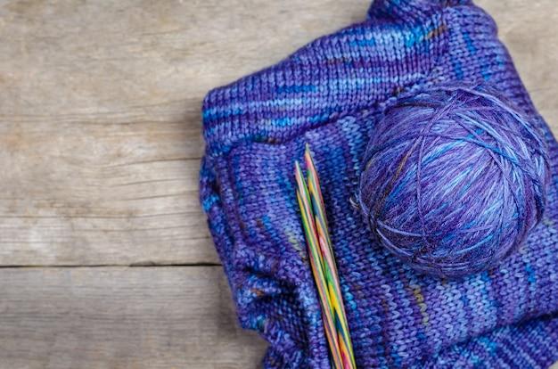 木製の背景に編み物のスレッド。編み物用アクセサリー。
