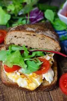 Сэндвич с темным хлебом, яйцом и помидорами.