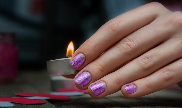 Женщина руки с розовым маникюром.
