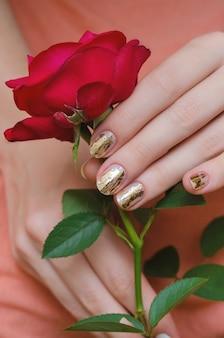 Золотой маникюр. женская рука держит красную розу