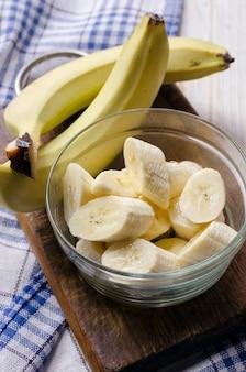 Нарезанный свежий банан в стеклянную емкость.
