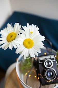 木の板にデイジーの花の花束と古いヴィンテージの素朴なカメラ。クローズアップ、ボケ。上からの眺め。