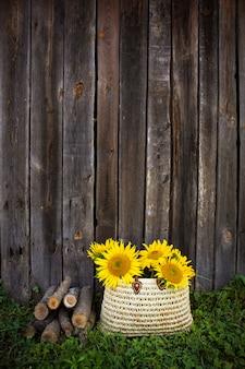 Бревна, букет подсолнухов в соломенной сумке стоят возле деревянного дома.