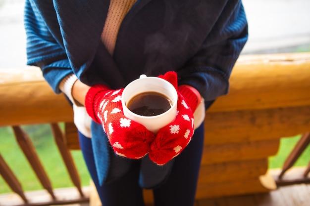 ミトンの少女はバルコニーのカルパチア山脈に立って、コーヒーを保持しています。
