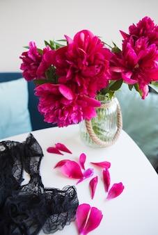 窓の近くの美しいピンクの牡丹、テーブルの上に花びらが崩れ、レースの下着