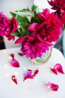 窓の近くの美しいピンクの牡丹、花びらがテーブルの上のライトで崩れる
