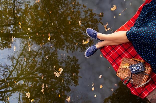赤いケージの格子縞の湖の近くの若い女の子の足。水の美しい反射。上からの眺め。