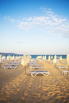 Красивый песчаный пляж с шезлонгами - отдых, море, солнце