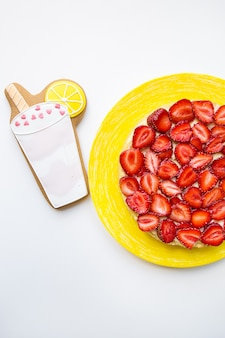 Яркий и вкусный клубничный торт стоит на столе вместе с печеньем в виде коктейля